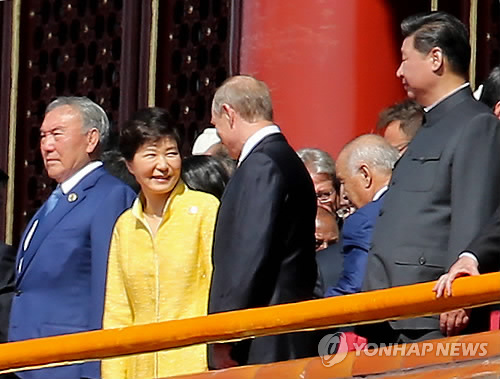 South Korean President Park Geun-hye (2nd from L) talks with Russian President Vladimir Putin (3rd from L) as they, along with Chinese President Xi Jinping (far R), stand to review a massive military parade marking the 70th anniversary of China`s victory over Japan in World War II at Tiananmen Square in Beijing on Sept. 3, 2015, (Yonhap)
