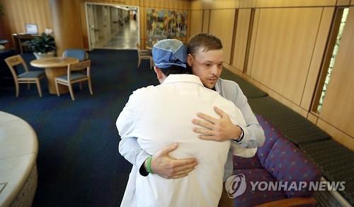 안면이식 수술 후 의사와 포옹하는 샌드니스