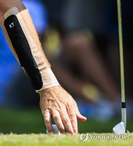 홀에서 공을 빼내는 골프 선수의 모습. [EPA=연합뉴스 자료사진]
