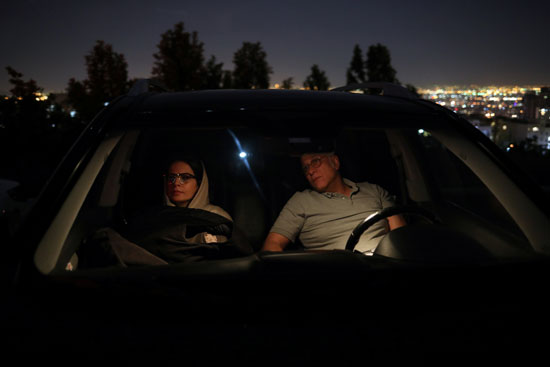 A man sits in his car next to his wife to watch the movie