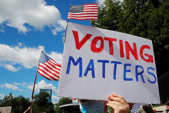 60555-متظاهر-يحمل-لافتة-تطلب-التصويت-على-القرار