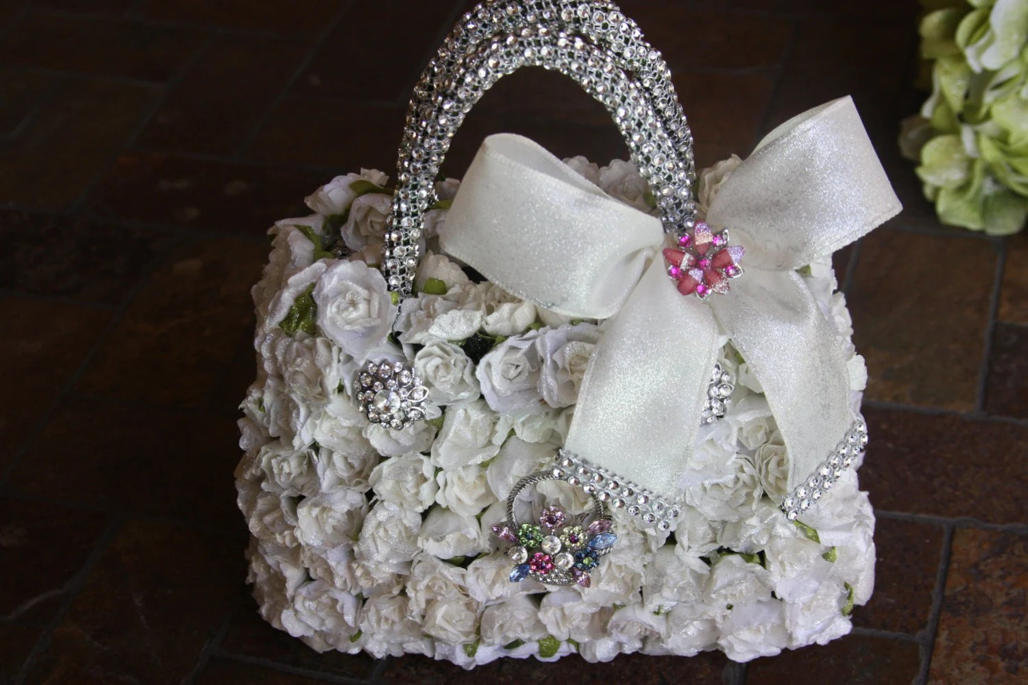 white flower girl basket with paper roses and brooches for