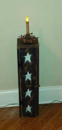 Primitive black toilet tissue holder cabinet with stars in the