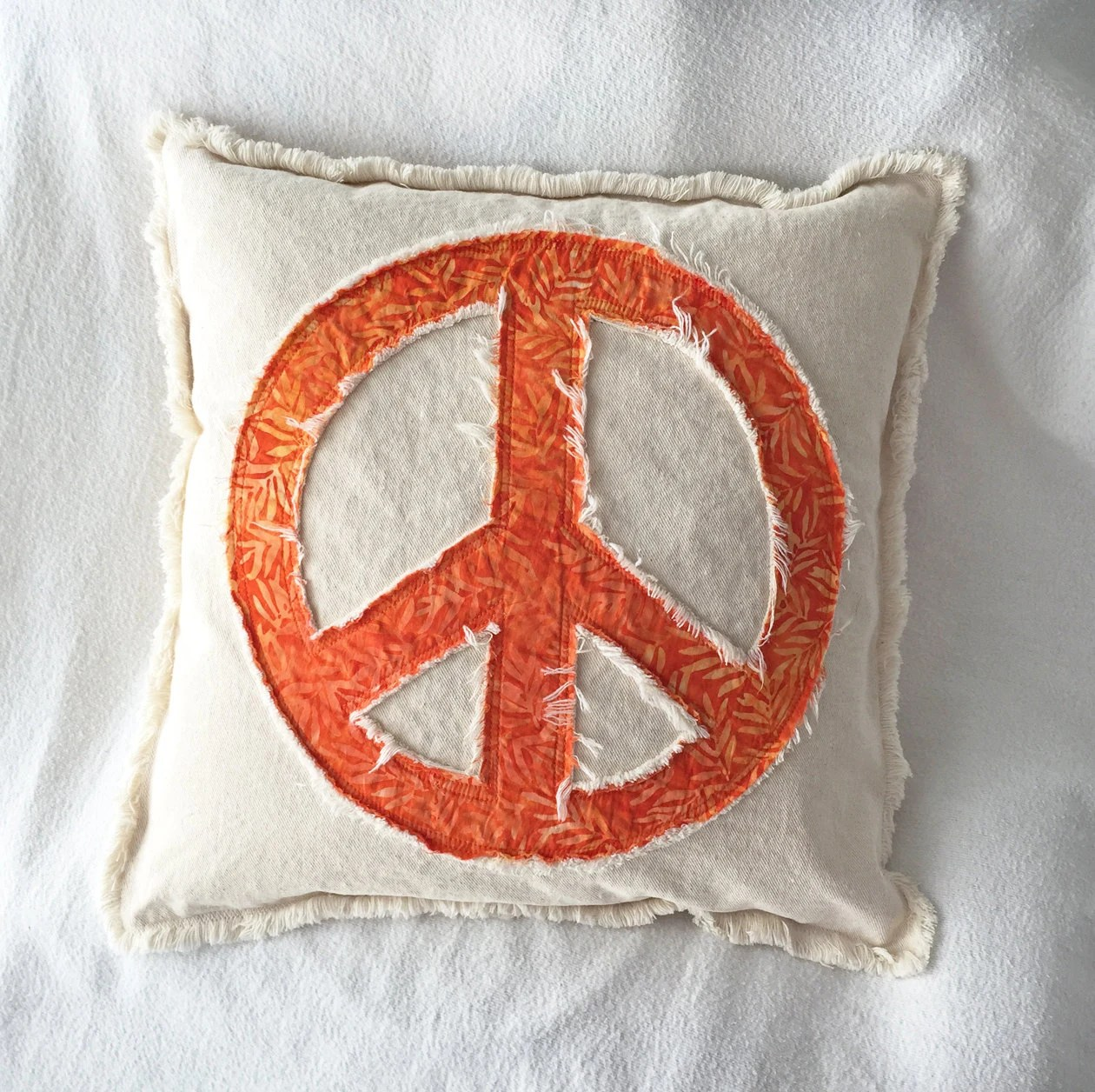 Peace sign pillow cover in orange leaf batik and distressed