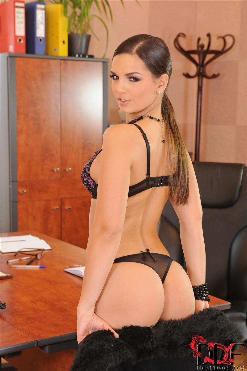 Eve Angel tickles her pink on the desk in black stockings