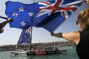 A supporter of New Zealand waves a flag as the Emirates Team New Zealand yacht returns to Port America's Cup.