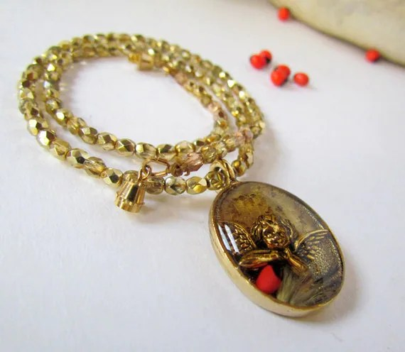 Resin Cherub Pendant Necklace golden beaded red seed