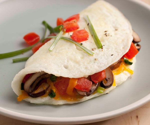 Healthy egg white omelet recipe with mushrooms, tomato, and cheddar cheese.