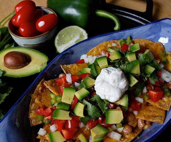 Healthy nachos with tomato, avocado, and cilantro