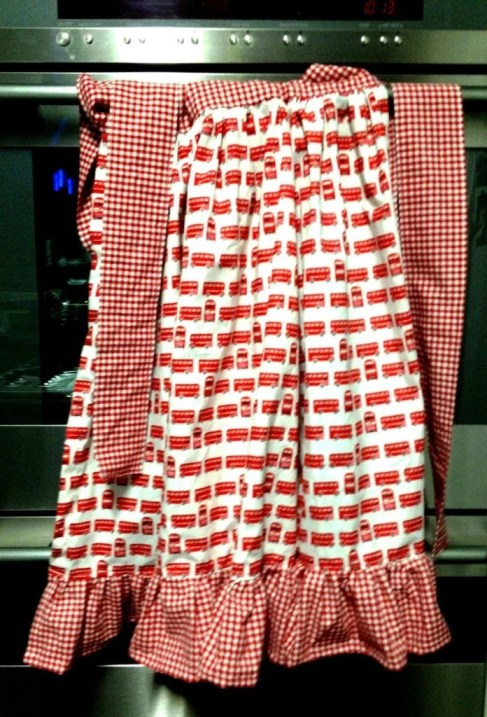 white apron with red bus pattern, red gingham ruffle and ties