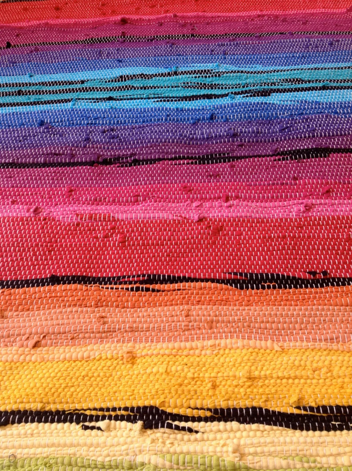 multicolored rainbow rug with black accents and