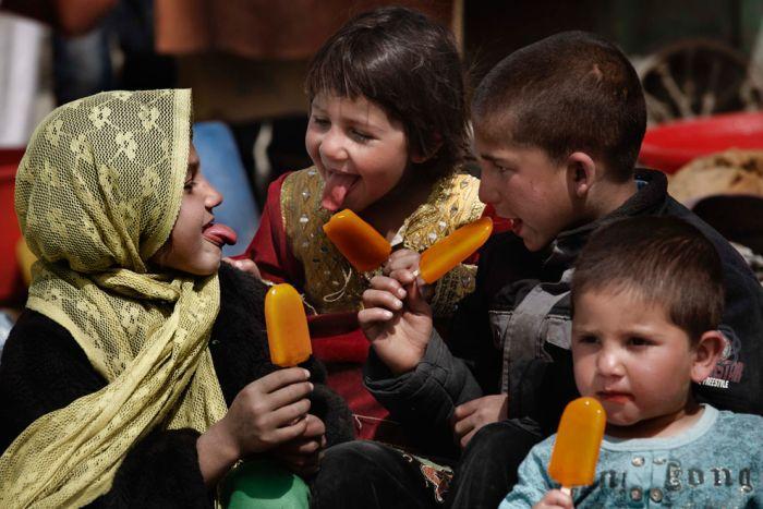 Дети показывают языки, покрашенные мороженым