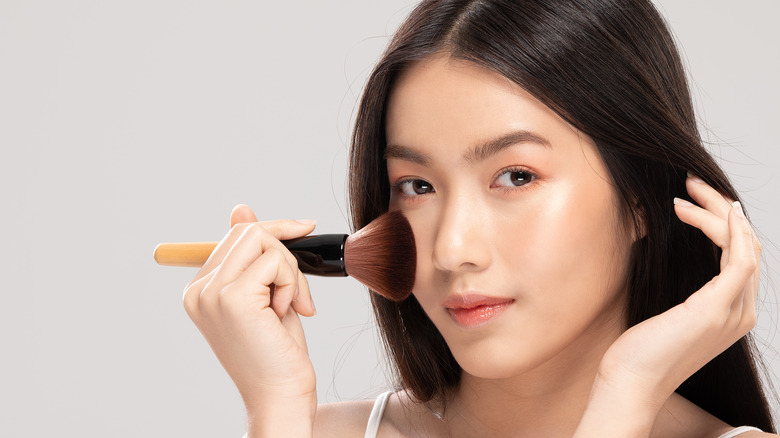 A woman holding a brush to her cheek