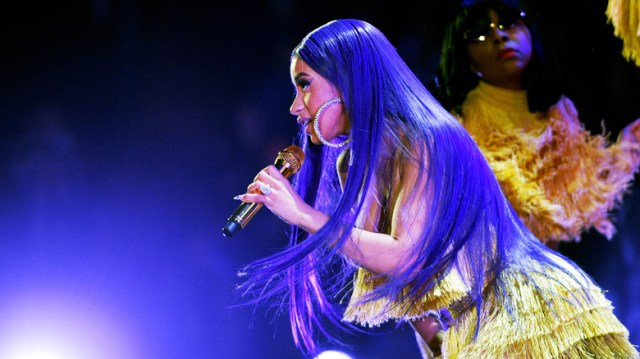 Cardi B performing with purple hair in 2018