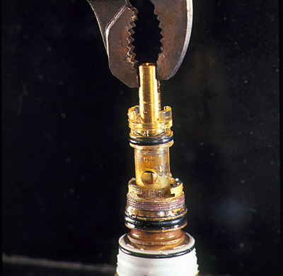 man using pliers to remove old faucet cartridge