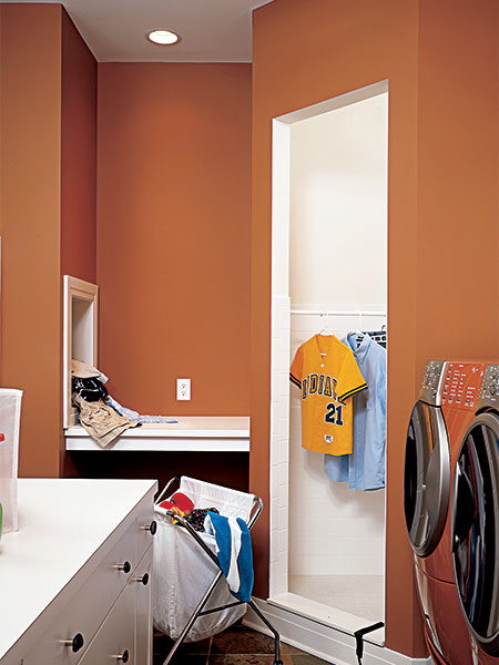 orange-brown walls and white trim of this modern laundry room with a the fold-down door of an open laundry chute visible at the back