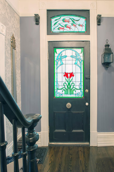 view down a hallway with a wood stair rail on the left, looking at an exterior door with red and green stained glass window and transom