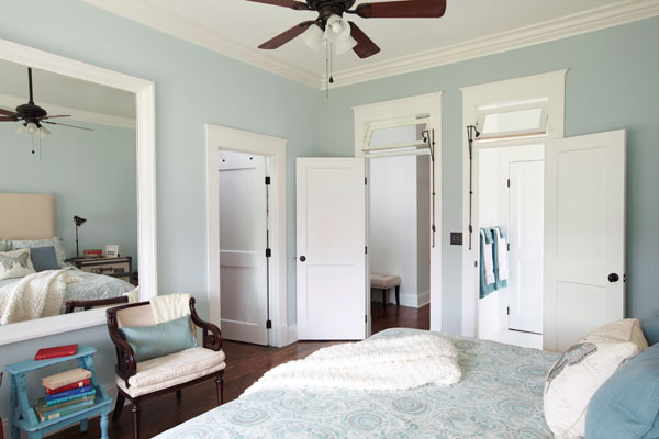 bedroom with pale, blue walls and two doors side-by-side, leading to other rooms each with a transom partially open over the door frame