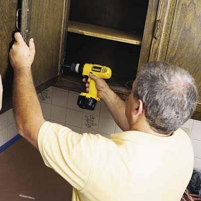 John Dee removing cabinet door with a cordless driver
