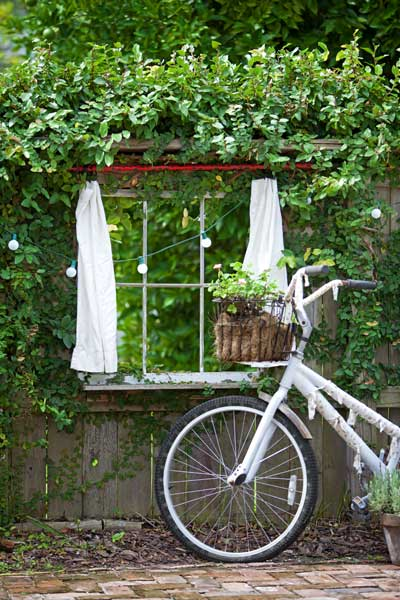 pictorial bicycle leaned against an outdoor, vine- and lights-covered window in an outdoor wall to illustrate nine Secrets of Cottage Style
