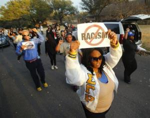 Darmita White holds a sign in Dallas to protest outside of the home of Parker Rice, a University of Oklahoma student caught on video in a racist fraternity chant, March 11, 2015.