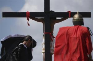 A Filipino penitent is nailed to a wooden cross as actors wait behind him during  Good Friday rituals at Cutud, Pampanga province, northern Philippines, on March 29, 2013.