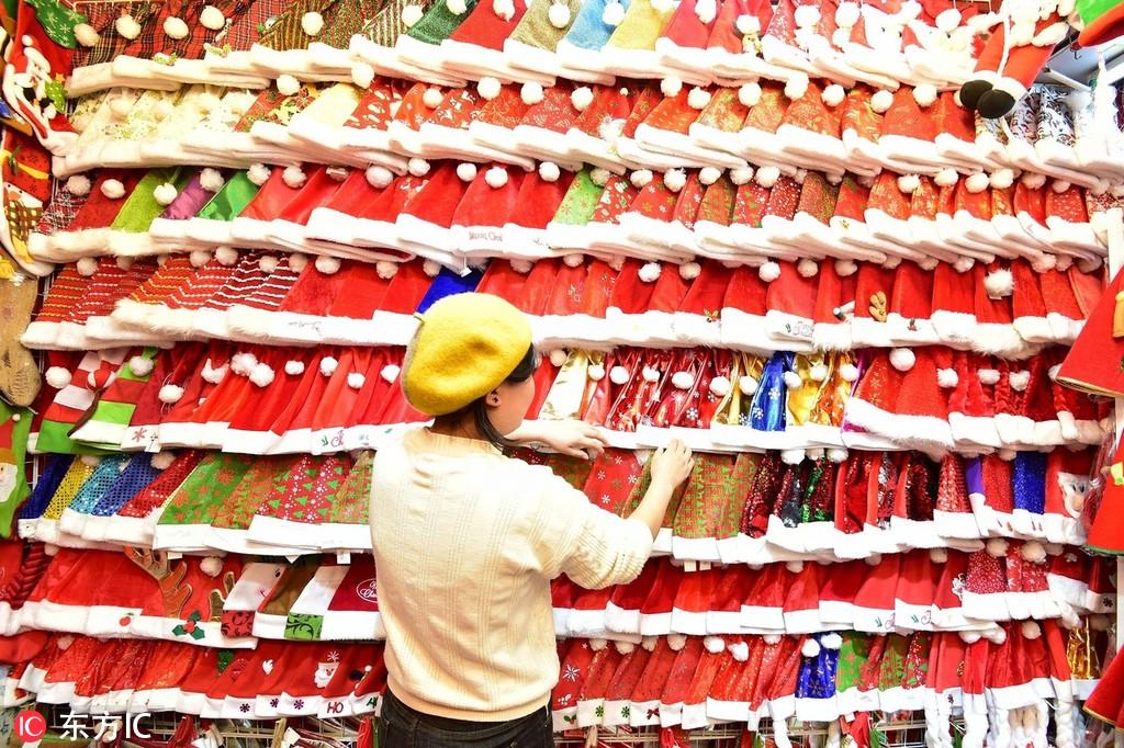 Shop keeper looking at hundreds of Santa hats | Yiwu International Trade City