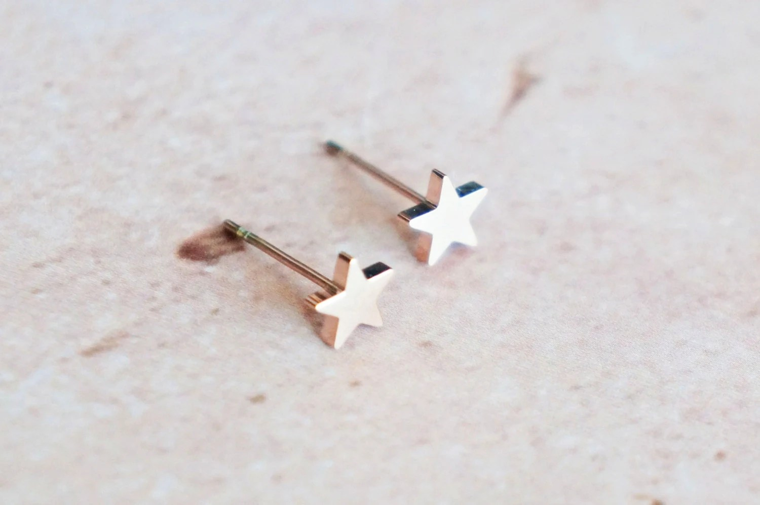 solid star stud earrings - rose gold titanium