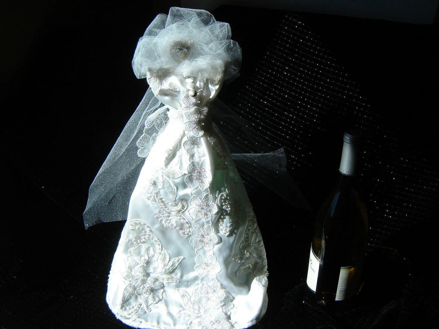 wedding gown wine bottle cover with satiny fabric and a veil with a sequined heart ornament