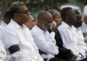 Haiti's President Rene Preval, second from left, wipes his tears as he attends a national day of mourning ceremony in Port-au-Prince, Friday, Feb. 12, 2010.