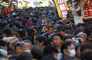 A girl takes a view of a crowded street from the shoulders of her father at Tokyo's famous Ameyoko market, jam-packed with year-end shoppers, Wednesday, Dec. 29, 2010.