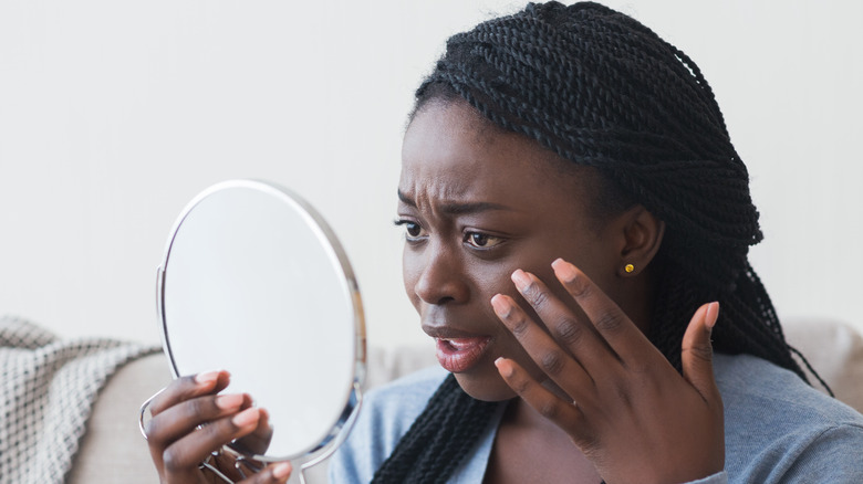 A woman looking in the mirror, concerned