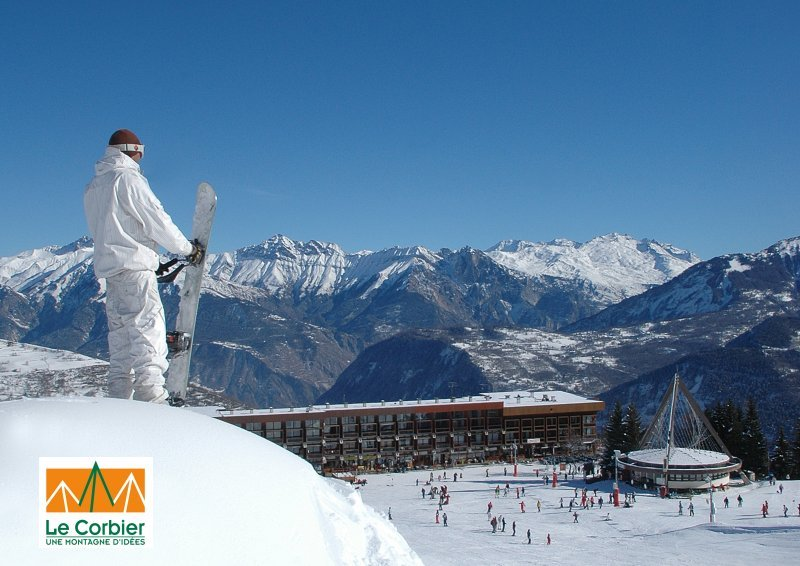 a snowboarder pausing to view the lodge at le corbier france