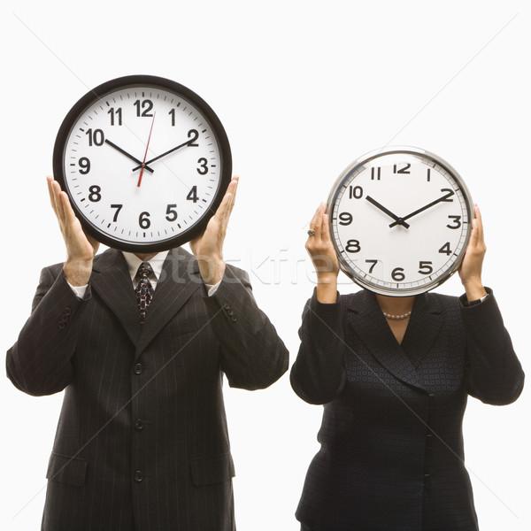 businesspeople holding clocks stock