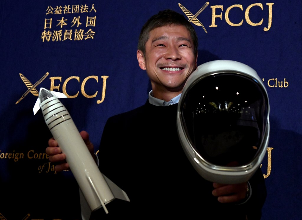 This file photo taken on October 9, 2018 shows Yusaku Maezawa, entrepreneur and then-chief of online fashion company Zozo and SpaceX BFR's first private passenger, poses with a miniature rocket and space helmet prior to start of a press conference at the Foreign Correspondents' Club of Japan in Tokyo.[File Photo: AFP]