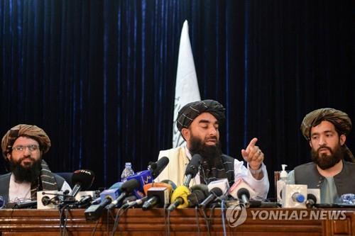 지난 17일 자비훌라 무자히드 대변인의 첫 공식 기자회견 때 동석한 탈레반의 문화위원회 소속 간부인 압둘 카하르 발키(오른쪽). [AFP=연합뉴스]