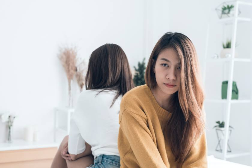 Young Asian lesbian couple argue and turn their back to each other in the period of sad in the bedroom. LGBT couple sulky to another in the bedroom with a sad mood. LGBT lover emotion concept.