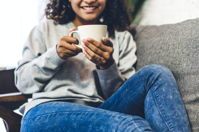 Young african american black woman relaxing drinking cup of hot coffee or tea on couch at home