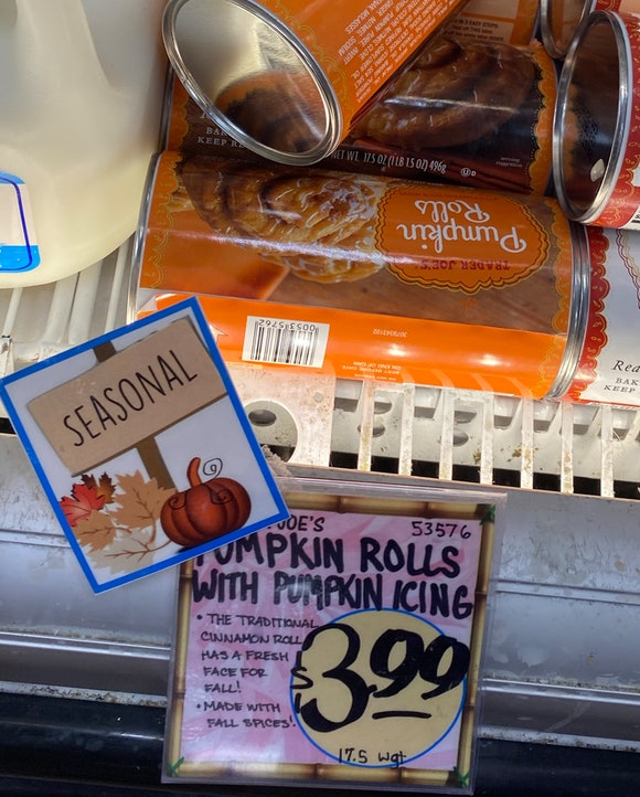 Images of a few tubes of pumpkin spice cream cheese roll behind a price tag.