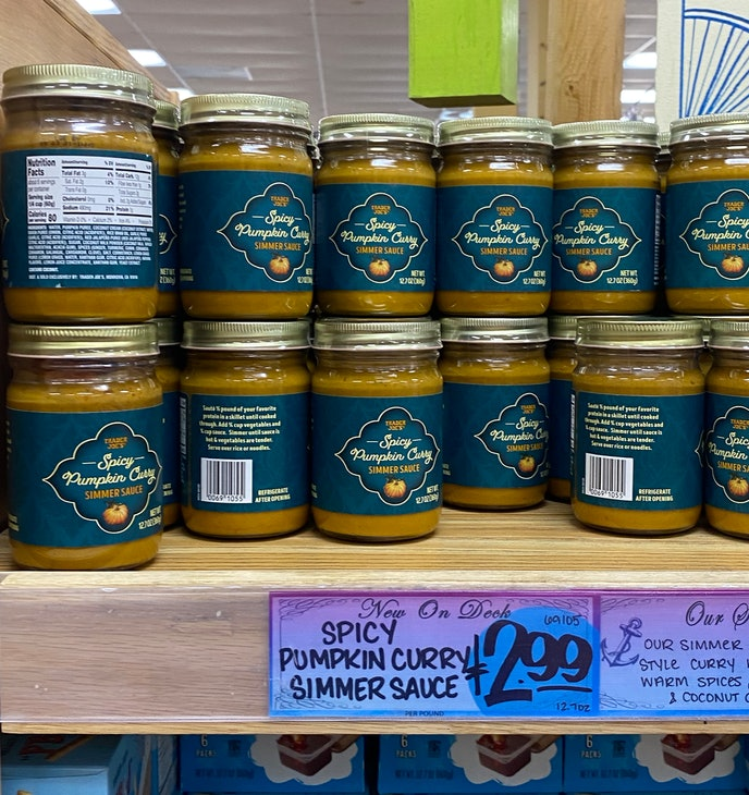 An image of several jars of brownish, pumpkin flavored curry on a shelf.
