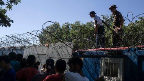 Ungarische Soldaten überwachen die Lebensmittelausgabe an wartende Flüchtlinge auf serbischer Seite. (Bild: ASSOCIATED PRESS)