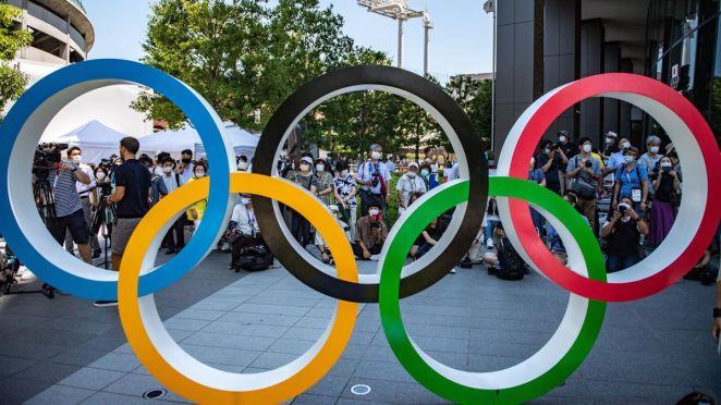Des personnes masquées derrière les anneaux olympiques, à Tokyo, le 21 juillet 2021