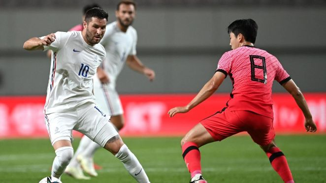 France's Andre-Pierre Gignac (L) is challenged by South Korea's Kim Dong-hyun (R) during their friendly football match in Seoul on July 16, 2021, ahead of the 2020 Tokyo Olympic Games.