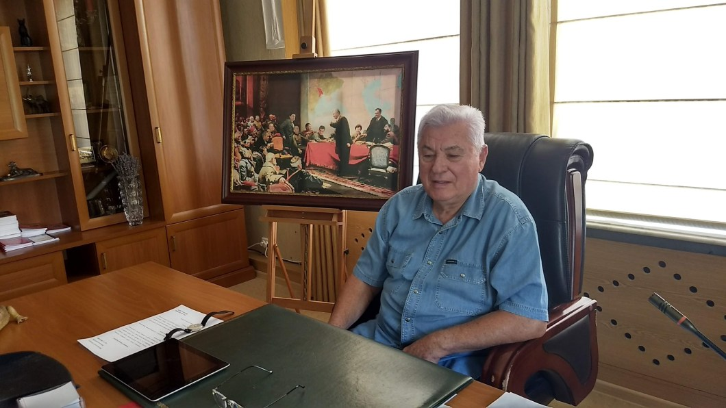 Ex-Moldovan President Vladimir Voronin, dressed in a bright blue shirt and sitting at a desk, in his office in 2019.