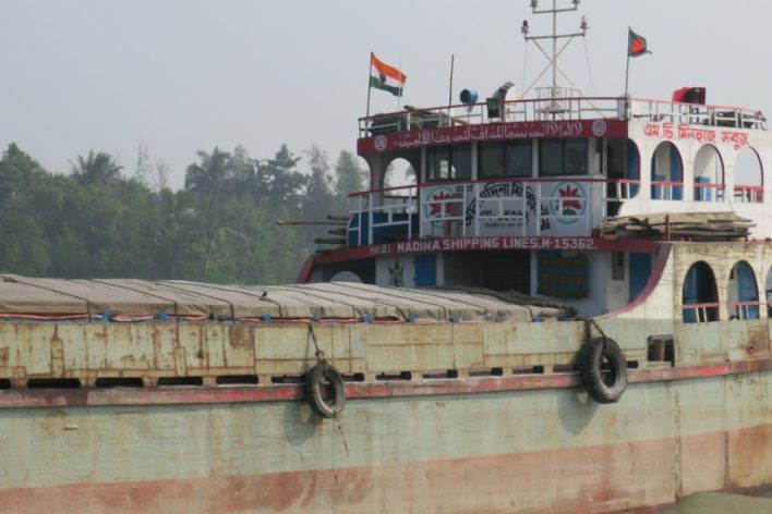 A ship carrying fly ash, with flags of India and Bangladesh. Photo by Namrata Acharya.
