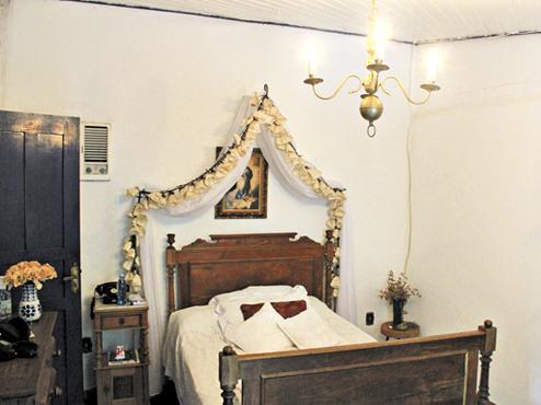 Flores, objetos religiosos e peças de antiquário são a base da decoração do quarto do casal. O destaque do espaço fica por conta do dossel, que emoldura a cama de madeira maciça (Talita Carvalho/CB/D.A Press)