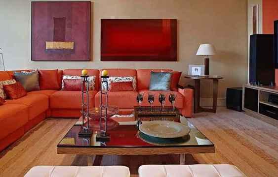 No projeto da Líder Interiores, assinado por Luiz Fernando Redo e Carlos Hansen, o sofá laranja tem almofadas de pluma sintética e estrutura metálica (Líder Interiores/Divulgação)