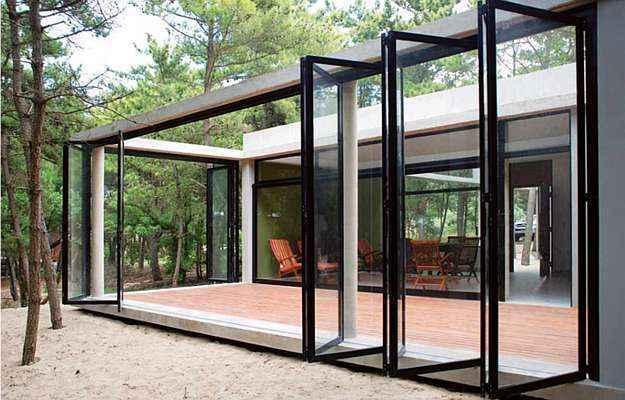 Os espaços livres são compostos por portas de correr e dobraduras que abrem e fecham conforme o período do dia   (Divulgação/Unoencinco Arquitetos)