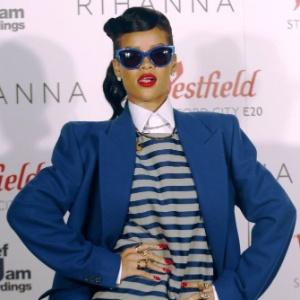 Vestida com conjunto listrado, Rihanna posa antes de cantar na inauguração da decoração de Natal de um shopping em Stratford, Londres (19/11/12)