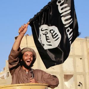 Militante islâmico balança bandeira do Estado Islâmico em Raqqa, na Síria